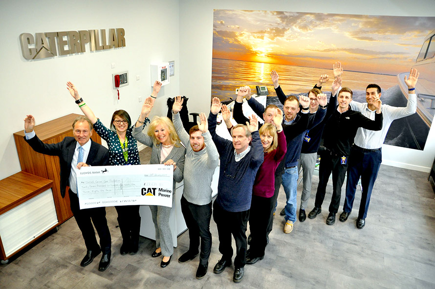 DCCF Chairman Chris Thomas (front left) and founder Eve Went (from right) receive a cheque from Jude Castell (front centre) and Caterpillar staff who have raised almost £30K for the local cancer charity.